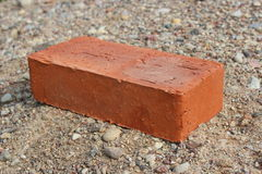 Red brick lying on the sand royalty free stock images
