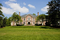 Red Brick Mansion on Green Grassy Hill Stock Photography