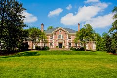 Red Brick Mansion on Green Grassy Hill. A large estate on top of a green grassy hill royalty free stock photo