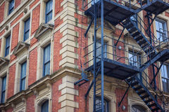 Red brick office or apartment building with metal fire escape. Stock Photos