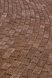 Red brick road. A road made of red bricks curving to the left stock photo