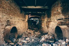 Red brick ruined abandoned underground sewer tunnel with dramatic mysterious atmosphere, inside sewerage. Dark toned royalty free stock image
