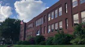 Red brick school building with American flag. A daytime summer establishing shot of a typical red brick school building in a small town. American flag waving on stock footage