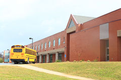 School Bus in front of Building. Red Brick School Building with Yellow School Bus at the front, ready for transporting students to home or drop off Stock Image