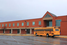 School Building with Bus. Red Brick School Building with Yellow School Bus at the front, ready for transporting students to home or drop off Royalty Free Stock Photography