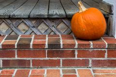 Orange pumpkin on patio stairs royalty free stock photography