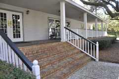 Red brick steps. Wth a white wooden railing, leading to a large outdoor covered porch Stock Images