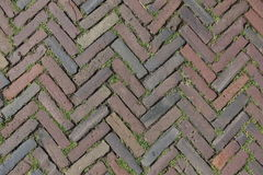Red Brick Street Road Paving Arranged Across Herringbone Background. Street made of old red bricks arranged across with grass in the gaps Stock Photography