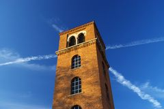 Red Brick Tower On A Field Of Blue Sky. Red brick building intersected by contrails on a deep blue sky Stock Image