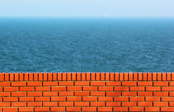 Red brick wall against blue sea background. Distant ship seen on Royalty Free Stock Photo