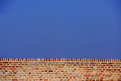 Red Brick Wall Against Blue Sky Royalty Free Stock Photography
