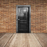 Red brick wall, black door and wooden floor Royalty Free Stock Photography