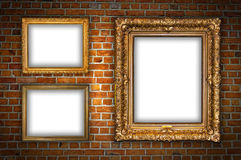 Red Brick Wall with blank frames. Old ornate golden frames hanging on a brick wall Royalty Free Stock Image