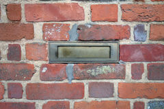 Red brick wall with a brass letter box Stock Photo