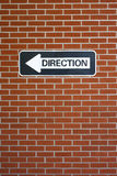 Red brick wall with direction sign. Royalty Free Stock Images