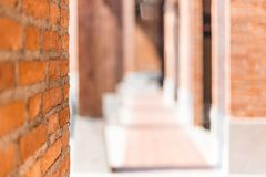 Red brick wall in foreground with blurred hallway background. Red brick wall in foreground showing rough brick texture, with blurred hallway background Royalty Free Stock Photo