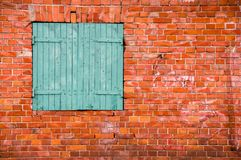 Red brick wall with a green window Stock Image