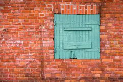 Red brick wall with a green window Stock Photo