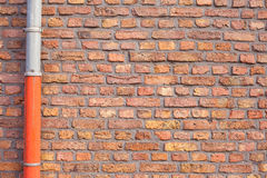 Red brick wall with gutter pipe Royalty Free Stock Images