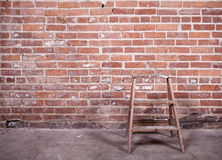 Red brick wall and ladder. Small wooden ladder standing empty in front of a red-brick wall Royalty Free Stock Image