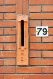 Red brick wall with mailslot and number Stock Photo