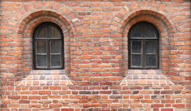 In a red brick wall of the medieval castle there are two narrow Stock Photo