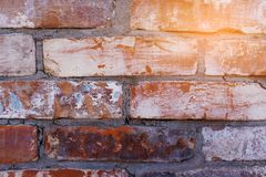 Red brick wall old dirty with peeling plaster. Dilapidated facade of the building with damaged plaster. Abstract banner. Brickwork. Background. Texture. Close stock image