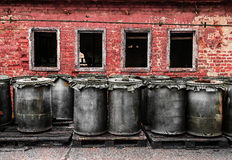 Red brick wall with plastic barrel outdoors Royalty Free Stock Image