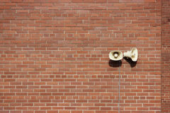 Red brick wall of a residential building and two loudspeakers. Red brick wall of a residential building and two loudspeakers stock photo