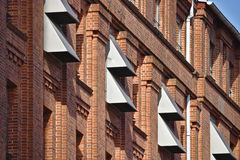 Red brick wall with row of narrow windows and metal wall vents. Sunlit red brick wall with narrow windows and metal air-conditioning wall vents Royalty Free Stock Images