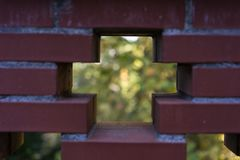 Red brick wall see through with cross and garden background Royalty Free Stock Photography
