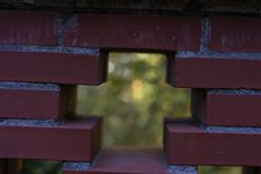 Red brick wall see through with cross and garden background Stock Image