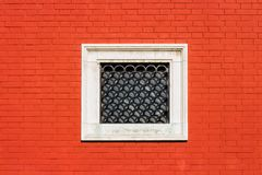 Red brick wall with small white window Stock Photo