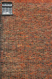 Red brick wall with small window. Urban brick wall texture background with small window in top right corner Stock Photos