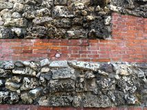 Red brick wall with stone inserts. Grungy red-brown old brick walls with  stone inserts shabby structure Stock Images