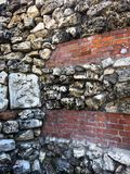 Red brick wall with stone inserts. Grungy red-brown old brick walls with  stone inserts shabby structure Royalty Free Stock Photos