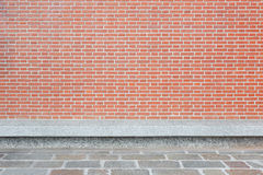 Red brick wall with stone tiled floor and bench Stock Image