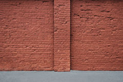 Red brick wall with the strip of asphalt and vertical column. Royalty Free Stock Photos