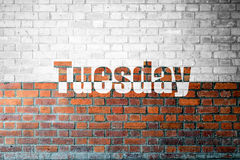Red Brick wall texture with a word Tuesday Royalty Free Stock Photos