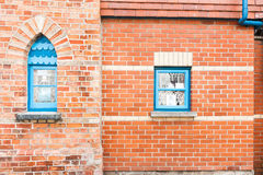 Red brick wall with two blue windows. Stock Photos