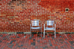 Red Brick Wall and Two Metal Chairs Stock Photography
