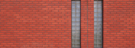 Red brick wall with two tall windows Stock Image