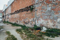 Red Brick Wall with Unfinished Wall Painted from The Street of George Town. Penang, Malaysia Royalty Free Stock Photos