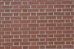 Red brick wall with white grouting. Brick wall consisting of various shades and sizes of red bricks. Bricks are held together with a visible white or gray Royalty Free Stock Photography