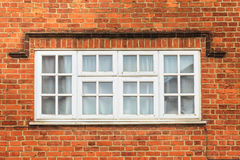 Red brick wall with white window Royalty Free Stock Photo