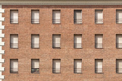 Red brick wall with white windows pattern. Stock Image