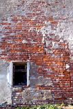 Red brick wall with window. Old red brick wall with close window and pieces of plaster Stock Photos