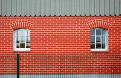 Red brick wall with windows. A new red brick wall with two windows Royalty Free Stock Photo