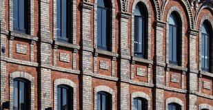 Red Brick Walls and Dark Windows. Rows of windows set into red brick walls Stock Photography
