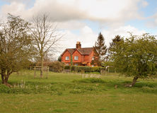 Red Bricked cottage in an english rural landscape Stock Images